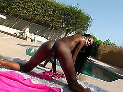 Hot ebony tranny Tameka is relaxing outdoors next to a pool by stroking her hard dick