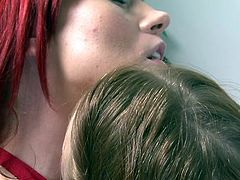 These two sexy redheads enjoy a nice make out session. One is a natural redhead and the other is a redhead with a dye job. They kiss each other hard in the living room and run their tongues over each other's lips.