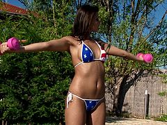 Sweet brunette girl in stars and stripes bikini does the exercises by the pool. After that she lies down on a lawn and fingers her pussy in close-up scenes.