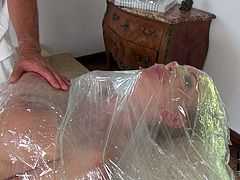 This busty brunette must have done something very bad. Spoiled nympho finds herself restrained this time on a massage table, completely naked but then gradually covered in a clear wrap. Horny dude puts his skills to the test stimulating his slave's pussy with vibrator.