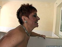 Cheesecake red-haired mom picked up an insatiable young dude in the club. He eats her bald delicious pussy before she kneels down to suck his massive cock.