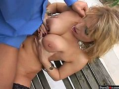Blonde cougar Jara Romain gives awesome titjob on a bench outdoor. Then she gets on top of harness. Later she sits on a real cock. She jumps like crazy fucking in reverse cowgirl position.