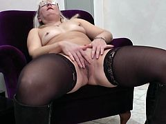 She took a sit on that arm chair and started to relax. The blonde mature Pamela began by slowly rubbing her tits over the bra and then she removed her black panties, revealing a big hot booty. The whore is really turned on now and her bald pussy craves for satisfaction! Enjoy what she's about to do!