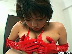 Playful Japanese cutie in passionate red lingerie and hands covered with latex gloves stands on her knees in front of horny dude giving him a titfuck before she rubs it with her feet covered with fishnet stockings in pov sex scene by Jav HQ.