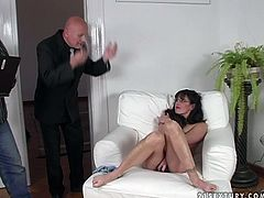 Lascivious brunette wench wearing glasses is sitting naked on a couch with her legs wide open. She inserts long dildo into her clam poking it in and out fast. Later, she is face fucked.