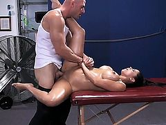 Pretty young brunette chick Diamond Kitty is lying on massage couch and getting her boobs oiled up and asshole cussed out by Johnny Sins.