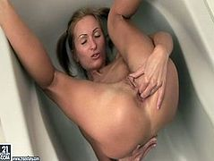 Spoiled skinny brunette hussy gets lured by pervert dude. He forces her to get inside the bathtub and lies on her back with legs pulled towards her head while he directs powerful stream of hot water on her ruined pussy.