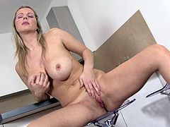 A busty blonde mature bitch gets naked in the kitchen and starts fingering her pink-ass motherfucking pussy! Check it out!