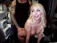 Petite blonde girl with small boobs gives a blowjob in a storeroom. Then she sits down on a chair and gets fucked deep in her shaved pussy.