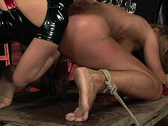 Dominant horny bitch ties up busty submissive blondie with ropes. This submissive girlie bends over the wooden table and gets her wet pussy polished with a dildo. Then rapacious bitch puts some metal clothespins onto the back of immobilized blondie.