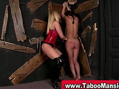 This dominant blonde bounds her slave with rope and spanks her with a paddle. After that, she fingers her ass hole.