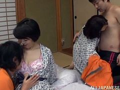 Two Asian women take their traditional Japanese clothes off and lie down on the floor. They get fucked hard in group sex video.