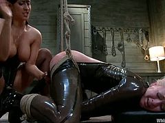 Isis Love is dominated by a busty brunette Shae Simone. She makes her wear that latex ninja suit with a strapon on it. Then she arches her and rides that tool!