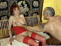Trashy mature woman is wearing red corset and nylon stockings. She opens her legs wide giving the guy total access to her privates. He plays with her mound using various sex toy. Hussy mature mom cums quivering with joy.