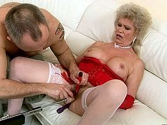 Wanton blond mature BBW in passionate red lingerie and white stockings sits on the couch with legs wide open getting her beareded pussy fucked with dildo drill and her clit stimulated with a vibrator in sizzling hot sex video by 21 Sextury.