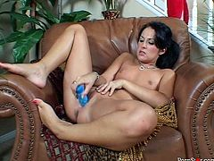 Lustful brunette hottie sits in the armchair with her legs pulled up while poking her shaved pink cunt with a dildo what makes her moan with pleasure in steamy solo sex video by Pornstar.