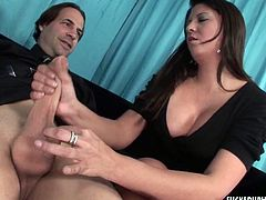 Sexy brunette having plump breasts stands on her knees and jerks off stiff dong intensively. She plays with his shaved balls and licks his hard penis.