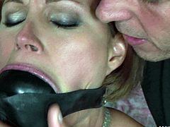 Obedient brunette hussy gets bandaged by insatiable dude and suspended to the bar before he plugs her mouth with a strange looking thing in BDSM-involved sex video by 21 Sextury.