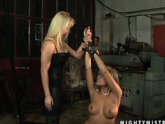 Kinky slim blond head in black tight dress ties up the other blond haired dyke with ropes and makes her kneel down. Then spoiled chick rubs and tickles her wet pussy passionately right on the dirty floor.