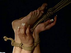 Kinky black haired gal with nice tits gets tied up with ropes. Her legs are pulled high up. Horny dude pours melt hot wax onto her butt causing her loud groans of pain and delight.