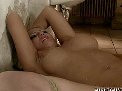 Ardent busty blonde hussy naked Sara lies on her back with legs wide open and hands tied above her head while a perverse mistress pokes her soaking cunt with a massive dildo in BDSM-styled sex video by 21 Sextury.
