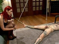 Tied on the floor and completely naked, Rukus experiences what a devilish redhead can do with a man. She tied his dick really hard with a rope and then, stepped on it with her high heels. The hot redhead bitch taunts him and wants to destroy his self esteem, before giving this guy some more pleasure. Enjoy the show