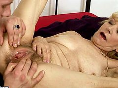 Shabby looking red-haired granny stands in doggy pose allowing a horny young dude tongue fuck her hairy pussy before he drills it from behind and later in missionary style.