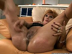 Hussy jade of mature age is oiled up all over. She sits on a couch spreading her legs wide. Perverted man drills her cunt with screwer with dildo head. Then he fingers her butt hole actively.