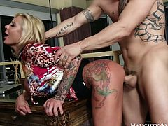 Bosomy mind taking blond MILF bends over a kitchen counter to get her cunt polished by tattooed bald dude and later banged from behind in steamy sex video by Naughty America.