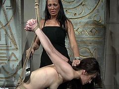 Insatiable brunette domina bandages a foxy brunette chic and suspends her in the air before she takes a dildo to pound her shaved cunt in BDSM-involved sex video by 21 Sextury.