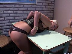 Slender blond babe bends over a table to demonstrate her ass