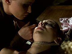 Spoiled brunette is securely tied to a wooden table. Cruel mistress knows how to teach this slut some manners so she clamps clothespins on her slave's swollen nipples.