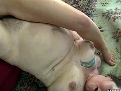 Ample old BBW lies on the floor with legs pulled on a couch while a skanky brunette chic tongue fucks her bearded pussy with pleasure.
