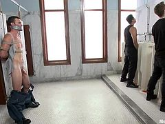 Tied up dude gets a handjob and a blowjob in a restroom. Then he also gets his ass fingered by two other dudes.