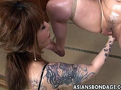 This Asian cutie is suspended in the air with her legs spread. Her heavily tattooed mistress is fisting her hairy cunt.