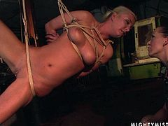 Shameless blondie hangs suspended by ropes. Horny mistress fingers her pierced snatch tenderly and sensually pushing her to the edge of powerful orgasm.