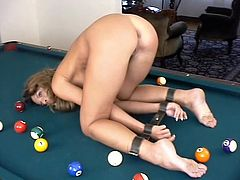 Sexy chick gets gagged and tied up by a man in a mask. She also gets her tits pinched and ass whipped on the billiard table.