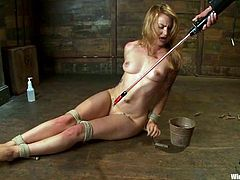 Payton Bell is playing BDSM games with Princess Donna Dolore indoors. She lets Donna tie her up and attach clothes pegs to her boobs and then gets her snatch pounded with a wired dildo.