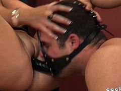 Check out this horny femdom slut having some fun with her slave. She makes him wearing a strapon on his mouth and fucking her tight snatch!
