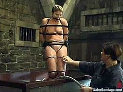 Horny fair-haired milf Vendetta is having a good time with Sir C in a basement. She lets the man bind and suspend her. The guy plunges the slut into a glass box filled with water and then rubs her cunt with a toy.