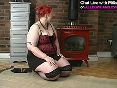 Saucy red haired girl with big boobs and fat ass takes off her clothes showing off her big plump body. She stuffs her fat pussy with smooth dildo poking intensively.
