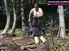Horny as fuck BBW bitch takes off her clothes under the open sky. Sitting on a stump she starts rubbing her clam with fingers intensively.