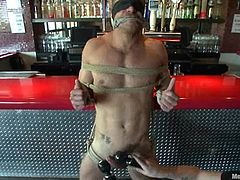 Muscular guy gets tied and blindfolded in the bar by two dudes. After that he gets a handjob and a blowjob. Then he also gets spanked.