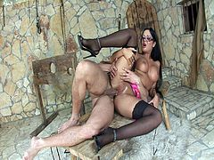 Claudia Rossi is wearing sexy lingerie and glasses when he starts sucking this guy's cock. He is laying on a wooden table and is surprised by her, so he cums rapidly. Then, he fucks her cunt and cums again in her mouth.