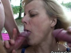 Watch horny old slut having fun with two young guy,She starts with sucking them off like crazy, Stripping and letting her chubby body be double-invaded with dick. Look how happy she is, and she can wash the cum off in the lake, too!