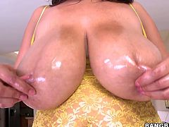 Slutty brunette mom with monster size boobs demonstrates her assets in front of camera. She has got her natural jugs oiled up. The guy weighs her tits though it is pointless. It is obvious her boobs are giant and heavy.