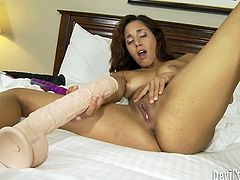 This curly haired nympho goes far and beyond to satisfy her lust. She fucks her swollen snatch with a massive, black dildo until she cums.