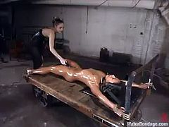 Hot brunette girl Jasmine Byrne is playing BDSM games with her GF in a basement. She gets tied up, drowned and tortured and then enjoys getting her pussy pounded with a fucking machine.