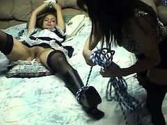 Naughty brownhead chick with slim body has got tied up to the bed. While she is lying motionless her mistress inserts big strapon in her wet pussy.
