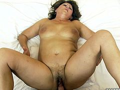 Kinky mature brunette strokes her plump tits and enjoys fucking. Fake cock fucks her hairy snatch intensively and makes her moan.